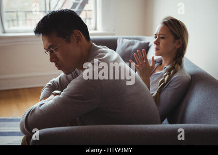 Unhappy couple arguing in living room - Stock Photo