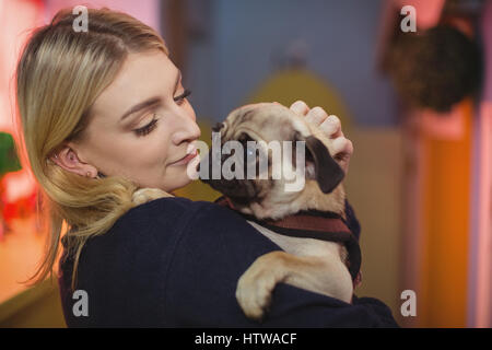 Woman carrying a pug puppy - Stock Photo