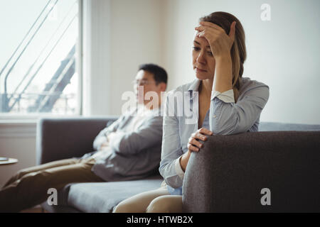 Couple sitting on sofa and ignoring each other - Stock Photo