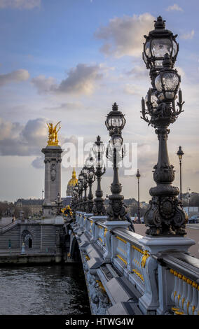 Lights along the Pont Alexandre III bridge over the Seine river in Paris, France.  View looking toward Musee de - Stock Photo