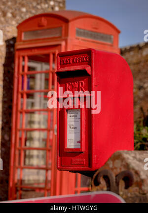 A red postbox and faded telephone box outside the village stores in the village of Firle in East Sussex near Lewes. - Stock Photo