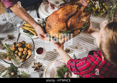 Close-up partial view of father and son holding roasted turkey at festive table - Stock Photo