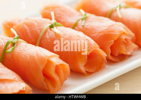 Rolls of smoked salmon with chives as a snack - Stock Photo