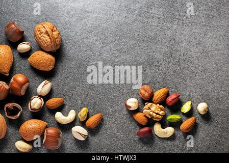 Almonds, walnuts, hazelnuts and pistachios on stone background - Stock Photo