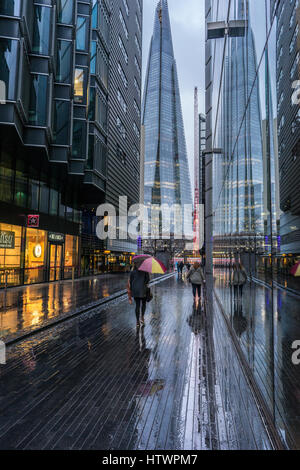 lady rushing by with umbrella in the rain in London city view of the Shard - Stock Photo