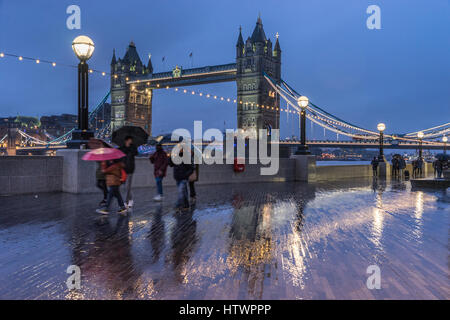 Family with umbrellas in rain rushing by with views of Tower Bridge London City - Stock Photo