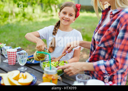 Happy girl dressing fresh salad with olive oil - Stock Photo