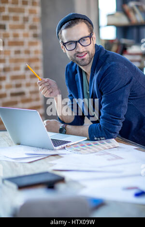 Smiling businessman with laptop - Stock Photo