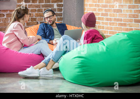 People in bean bag chairs - Stock Photo