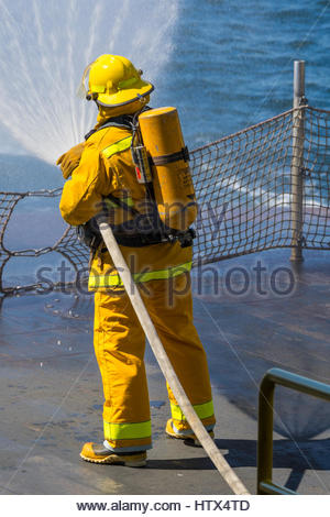 A firefighter, clad in turnout gear, aims a fan of water from a firehose off the back of a Washington State Ferry - Stock Photo