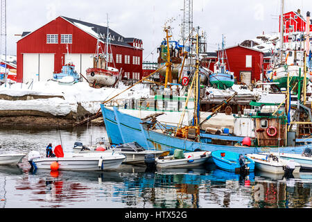 Boats and fishing ships standing on land and water in port of Sisimiut, Greenland - Stock Photo
