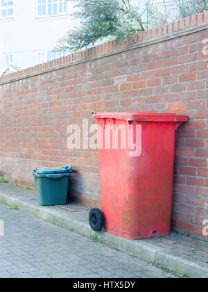 A red and green bin resting against a wall. - Stock Photo