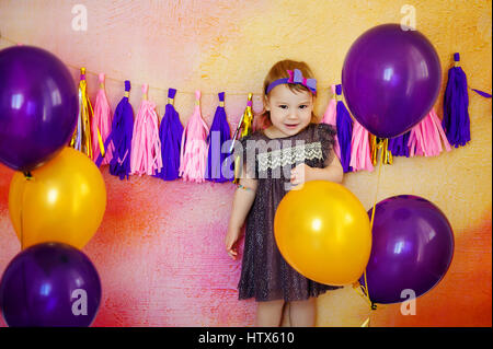 Cute girl with colorful balloons in room decorated for birthday party - Stock Photo