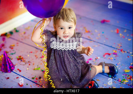 Cute baby girl 1-2 year old sitting on floor with pink balloons in room. Birthday party. Celebration. Happy birthday - Stock Photo