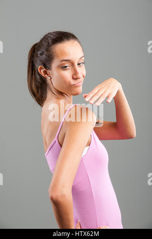 Young skinny woman in pink shirt looking back over her shoulder with a smirk, showing gesture with her hand, standing - Stock Photo