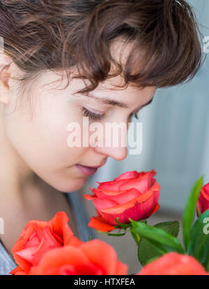Woman smelling red rose bouquet in vase inside profile - Stock Photo