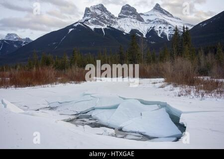 Three Sisters Snowy Mountain Tops in winter near Banff National Park in Canadian Rockies - Stock Photo