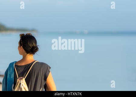 Young black haired woman looking up and down the beach with towel and back pack. - Stock Photo