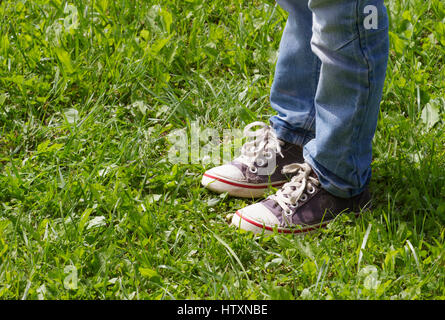 Boy in blue sneakers and jeans standing on the green grass in the park. Close up leg's shot. Top view. - Stock Photo