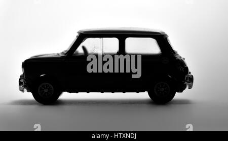 Die cast model of a mini cooper shot in a black and white silhouette. - Stock Photo