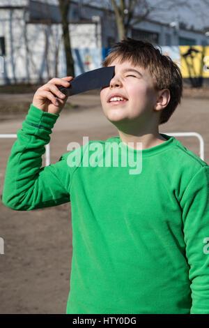 A boy watching a solar eclipse through a dark glass. Poland. - Stock Photo
