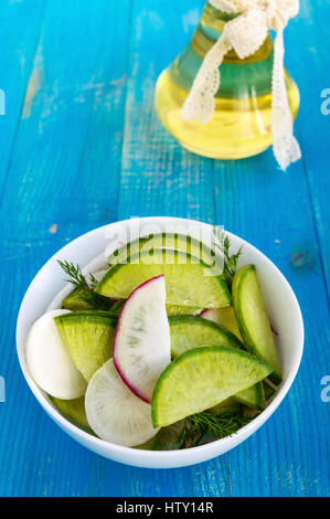 Salad of radish of different varieties (daikon, green, Chinese red) chopped slices, flavored with sunflower oil - Stock Photo