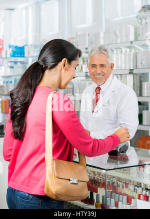 Chemist Looking At Customer Making Payment At Counter - Stock Photo