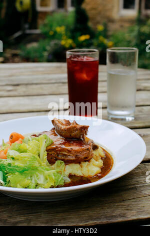 Lamb shank with vegetables on an pub outdoor wooden table, glass of water and juice next to it - Stock Photo