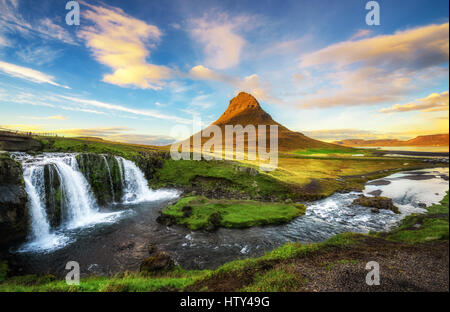 Summer sunset over the famous Kirkjufellsfoss Waterfall with Kirkjufell mountain in the background in Iceland - Stock Photo