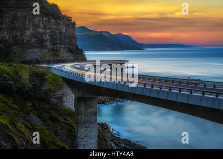 Sunset over the Sea cliff bridge along Australian Pacific ocean coast with lights of passing cars near Sydney, Australia. - Stock Photo