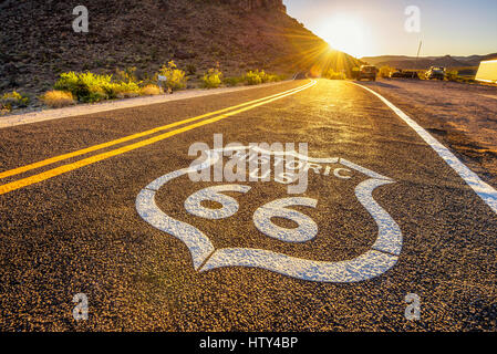 Street sign on historic route 66 in the Mojave desert photographed against the sun at sunset - Stock Photo