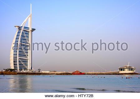 People enjoying the open Beach beside the iconic Burj Al Arab Hotel (left) and the 360 lounge bar (right), Dubai, - Stock Photo
