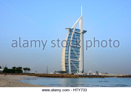 People enjoying the open Beach beside the iconic Burj Al Arab Hotel, Dubai, United Arab Emirates - Stock Photo