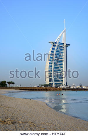 People enjoying the open Beach beside the iconic Burj Al Arab Hotel, Dubai, United Arab Emirates - Stock Photo