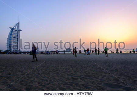 Sunset on Burj Al Arab with people playing football, chatting, walking etc.., Dubai, United Arab Emirates - Stock Photo