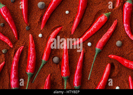A lot of the red hot chilli peppers and black peppers corns lying on a red paprika. a concept of spicy food and - Stock Photo