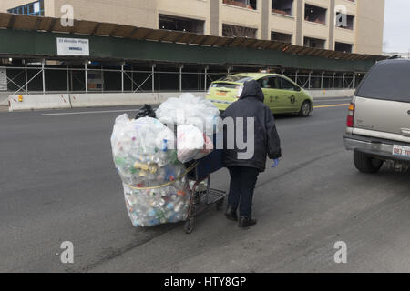 Female bottle & can collector working along Coney Island Avenue on a cold winter morning in Brooklyn, New York, - Stock Photo