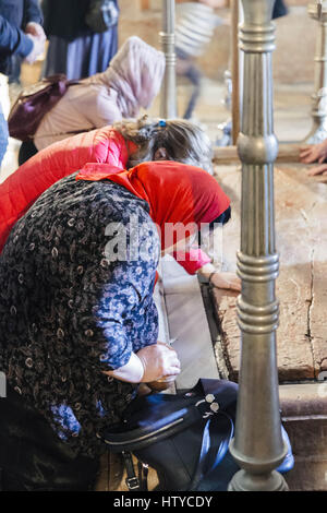 Women Kissing the Stone of Unction in the Church of the Holy Sepulchre in Jerusalem - Stock Photo