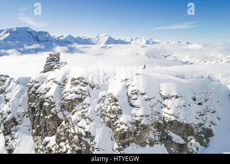 Man standing on snow covered mountain taking a dronie, Salzburg, Austria - Stock Photo