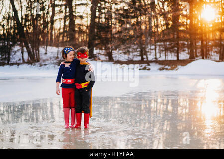 Boy and girl standing on frozen lake wearing superhero costumes - Stock Photo