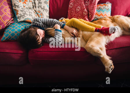 Girl sleeping on couch with golden retriever dog - Stock Photo