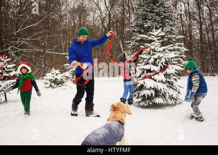Father and three children decorating a Christmas tree in the garden with golden retriever dog watching