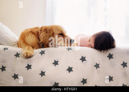 Smiling Girl lying on a bed next to a golden retriever dog - Stock Photo