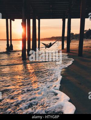 Teenage boy drinking water, in a hammock under the pier, Aptos, California, America, USA - Stock Photo