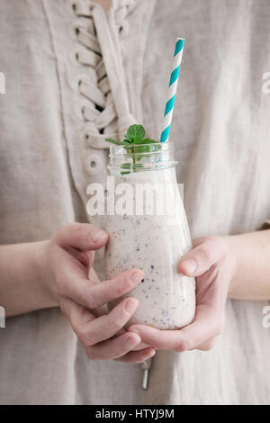 Bottle of smoothie with chia seeds, blueberries, mint leaves and retro striped cocktail tube in female hands. Woman - Stock Photo