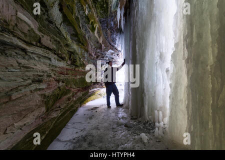 A man standing inside an ice cave formed behind Buttermilk Falls during the winter in Hamilton, Ontario, Canada. - Stock Photo