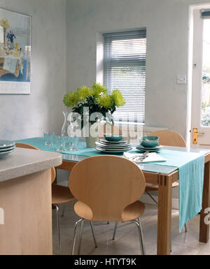 Kitchen With Conservatory Attached Vase Of Lime Green Chrysanthemums On Glass Topped Table A Turquoise Cloth In An Economy