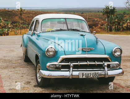 An old blue Chevrolet taxi in a car park on the outskirts of the city of Trinidad, Cuba - Stock Photo