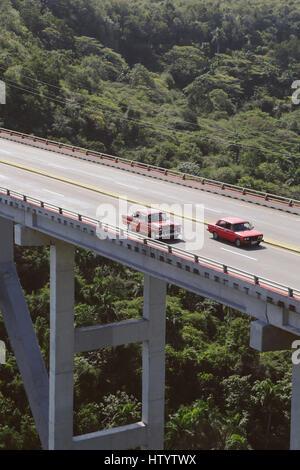 Classic American style cars driving across a bridge in Cuba - Stock Photo