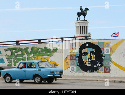 An old blue Lada car seen on the road by the Maximo Gomez Monument and street art depicting Che Guevara in Havana, Cuba